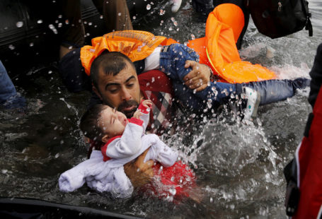 Syrian refugee holds onto his children as he struggles to walk off a dinghy on the Greek island of Lesbos